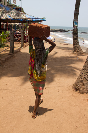head stones: The Indian woman in a sari stones for building on the head on a beach. India Goa.