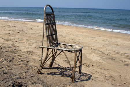 The lonely wattled chair costs on a beach, against the sea. GOA India beach. photo