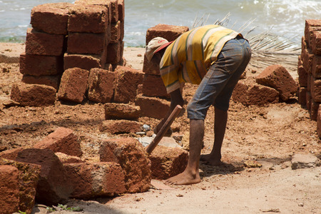 relies: The Indian man works at building. India Goa.