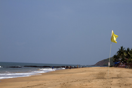 Beautiful sandy beach with a yellow flag. India Goa. photo
