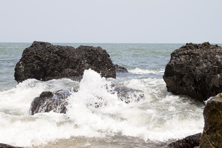 wavely: Beautiful waves of a beach of Goa, India. Wave crashing on the rocky reef. Stock Photo