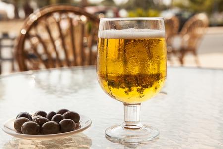 Aceitunas En Un Tazón Pequeño Y Un Vaso De Cerveza Helada En Una ...