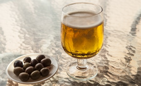 misted: Misted glass of beer with olives on a glass table.