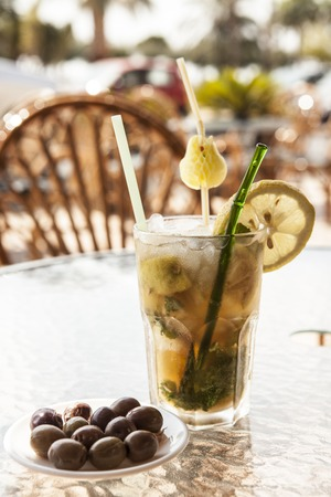 misted: Misted glass of mojito with olives on a glass table.