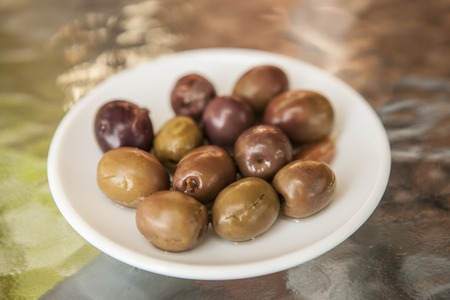 small plate: Ripe olives on a small plate. Snack bar. Stock Photo