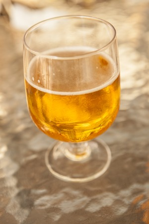 misted: Misted glass of beer on a glass table in a bar. Stock Photo