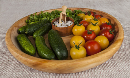 salt shaker: Fresh red and yellow cherry tomatoes and cucumbers with salt shaker on wooden tray in a rustic style. Good ingredients for the salad, cucumbers, tomatoes and green salad mix.