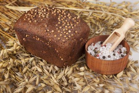 sal: Hogaza de pan casero con semillas de mostaza negra en una mesa con espiguillas de centeno y la sal agitador de sal.