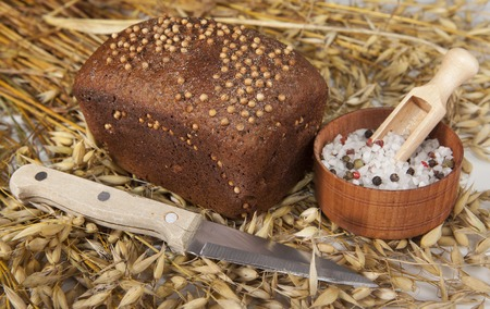 salt shaker: Loaf of homemade bread with black mustard seeds on a table with spikelets of rye and oat sand salt shaker salt and knife.