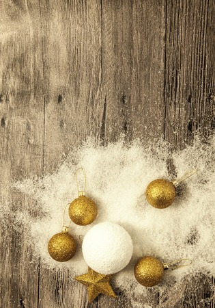 palle di neve: Glittering gold Christmas balls, snowballs, winter snow and star on wooden background.