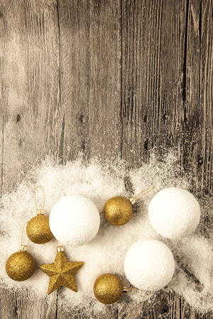 neve palle: Glittering gold Christmas balls, snowballs, winter snow and star on wooden background.