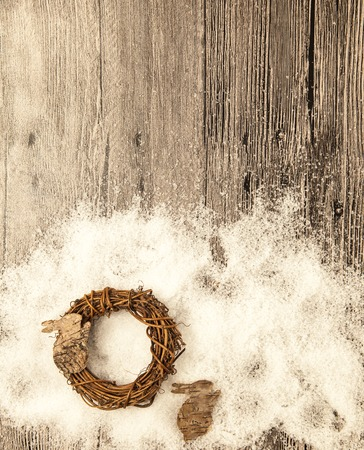 bark background: Christmas card with wreath and little hare from birch bark on a wooden background