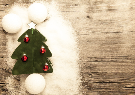 palle di neve: Postcard with a Christmas tree ,Christmas balls snowballs and snow on wooden background.