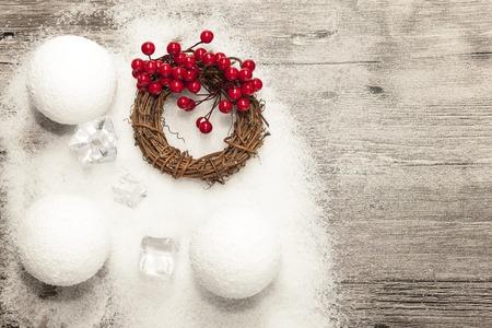 coronas navidenas: Tarjeta de Navidad con bolas de nieve y la nieve y guirnaldas de Navidad en el fondo de madera