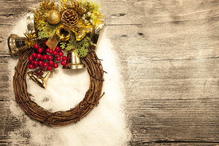 Glittering gold Christmas balls, bells,wreath, and star on wooden background with snow