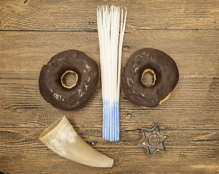 hannukah: Donuts goat horn candles and star of David Hanukkah symbols on wooden background. Jewish holiday hannukah symbols - menorah, doughnuts, chockolate coins and wooden dreidels. Stock Photo
