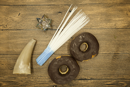 estrella de david: Donuts goat horn candles and star of David Hanukkah symbols on wooden background. Jewish holiday hannukah symbols - menorah, doughnuts, chockolate coins and wooden dreidels. Foto de archivo