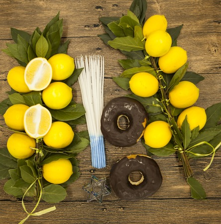 hanukiah: Branch lemons  donuts candles  crown of thorns and goat horn. Symbols of the great holiday of Hanukkah. On wooden background