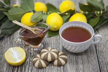 composed: Beautiful composed on wooden background Cup of tea lemon and  biscuits. Stock Photo