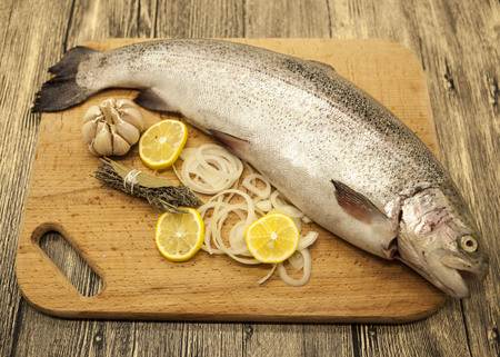 salmon fishery: Fresh Norwegian rainbow trout with lemon and onions on a wooden background.