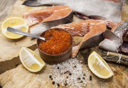 salmon fishery: Fresh Norwegian rainbow trout with lemon red caviar, sea salt and onions on a wooden background. Stock Photo