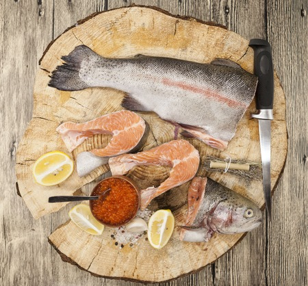 salmon fishery: Fresh Norwegian rainbow trout with lemon red caviar, sea salt, knife and onions on a wooden background.
