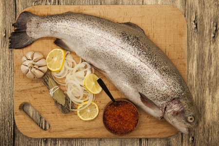 salmon fishery: Fresh Norwegian rainbow trout with lemon red caviar, and onions on a wooden background.