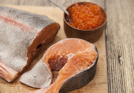 salmon fishery: Fresh Norwegian rainbow trout with red caviar on a wooden background. Stock Photo