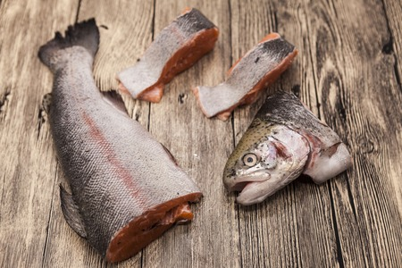 salmon fishery: Fresh Norwegian rainbow trout steaks lying on the wooden background. Stock Photo