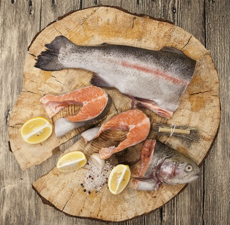 salmon fishery: Fresh Norwegian rainbow trout steaks with lemon lies on a wooden background. Stock Photo