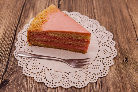 dessert fork: Fresh tasty sweet piece of pink cake on a white napkin and a dessert fork on a wooden background.