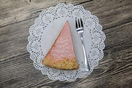 porcion de torta: Sabroso dulce Pedazo fresco de pastel de color rosa en una servilleta blanca y un tenedor de postre en un fondo de madera.