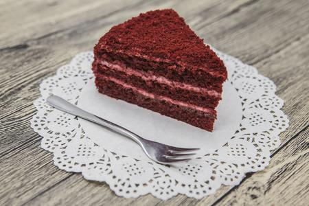 dessert fork: Fresh tasty sweet piece of  red velvet cake, on a white napkin and a dessert fork on a wooden background.
