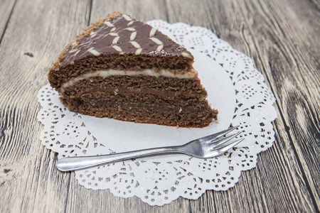 dessert fork: Fresh tasty sweet piece of  chocolate cake on a white napkin and a dessert fork on a wooden background.