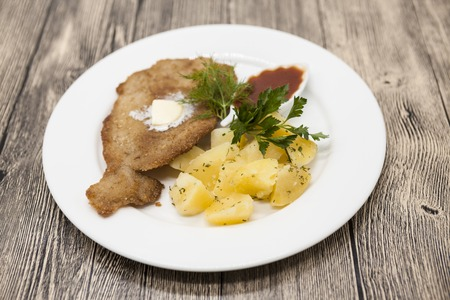 wiener: Petite Wiener schnitzel with boiled potatoes and ketchup. Served on a white porcelain plate on a wooden background