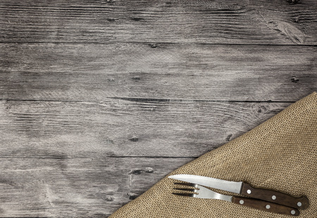 Beautiful wooden background with napkin knife and fork. Fine background for the menu of restaurants and cafes.