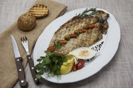 whitefish: Fried fish whitefish on plate with vegetables and bread with a fork and knife