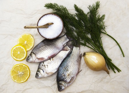 carassius gibelio: A  fresh carp live fish lying on a on paper background with a knife and slices of lemon and with salt dill. Live fish crucian Carassius auratus gibelio.