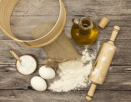 bolter: Wheat flour in a canvas bag,sieve, the olive oil in a glass carafe, a large salt shaker wood, raw eggs, a wooden rolling pin: set for making homemade bread dough on a beautiful dark wooden background.