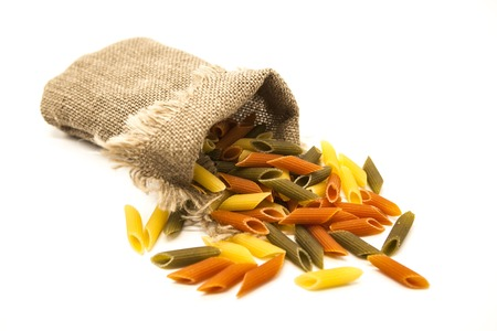 durum: Beautiful Italian pasta Penne rigate from durum wheat  in a linen sack, closeup on a white background. Stock Photo
