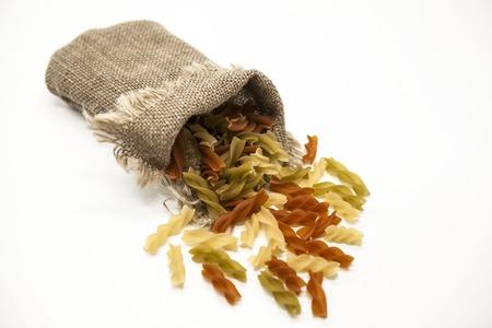 durum: Beautiful Italian pasta Fusilli from durum wheat  in a linen sack, closeup on a white background.