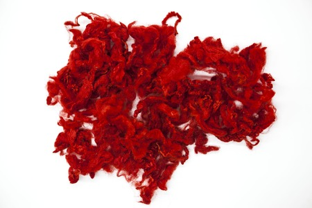 warmness: Red piece of Australian sheep wool Merinos breed close-up on a white background.