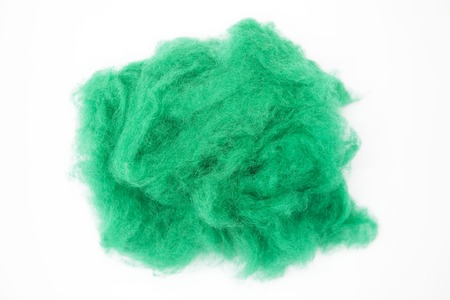warmness: Emerald  green piece of Australian sheep wool Merino breed close-up on a white background.