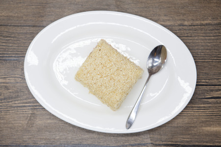 no food: Dukan Diet. Fresh delicious diet cake at Dukan Diet on a porcelain plate with a spoon on a wooden background