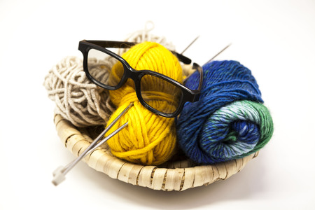 needle: Three ball of woolen threads, yellow, blue, beige and steel knitting needles and glasses in a wooden basket on a white background