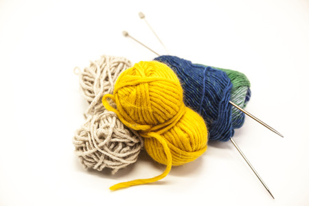 needle: Three ball of woolen threads, yellow, blue, beige and steel knitting needles  on a white background.