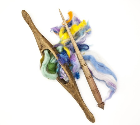 warmness: Colored hair and old spindle close-up on white background. Tools for knitting of wool.