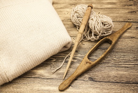 weave ball: Excellent mocap two old wooden spindle with a ball of wool thread for the manufacture of woolen threads on a wooden background.