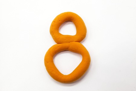 monotype: Orange  plasticine figure number eight 8 close-up on a white background. The icon for the Internet Stock Photo