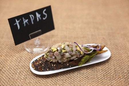 excellent background: TAPAS poster . Fresh, delicious Spanish tapas with Tartar of herring and onions on a black baguette. An excellent background for the menus, cafe, restaurant Stock Photo